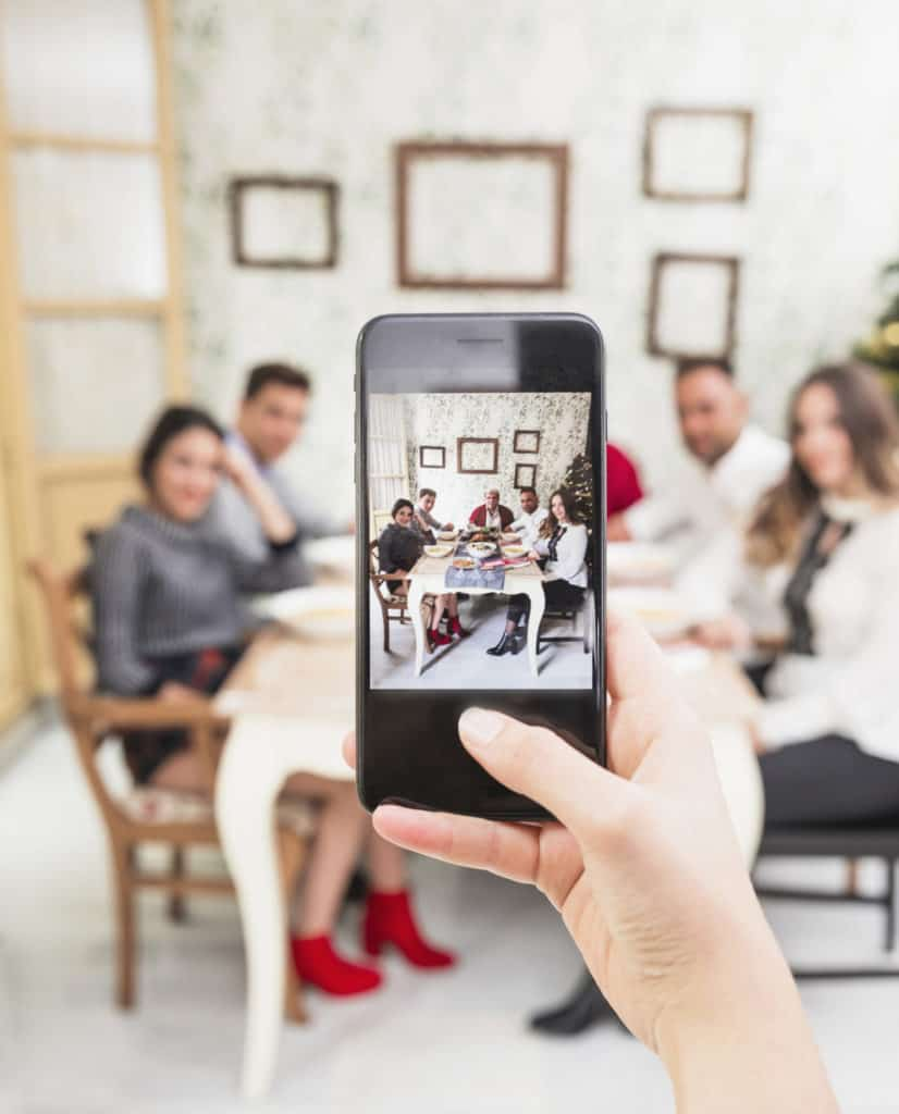 person-taking-picture-happy-family-festive-table-scaled-e1605902702944-826x1024-1